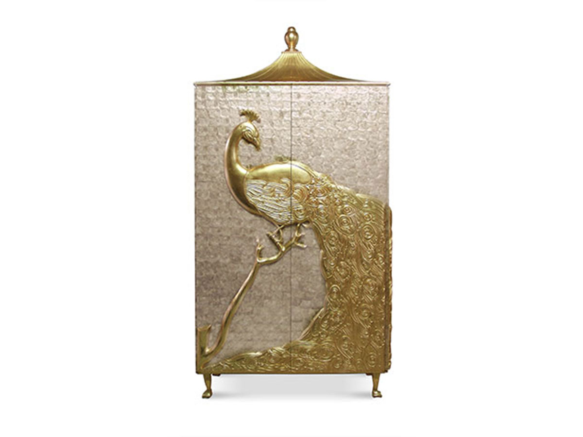 Inspired by the aristocratic palaces of the Alexandrian pashas of Egypt, the mother of pearl Camilia Armoire by Koket is crowned by artisan hand-carved peacock, meticulously engraved and delicately finished in metal leaf.
